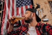 handsome repair station worker drinking beer at garage with usa flag hanging on wall