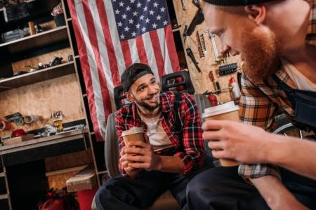 handsome mechanics drinking coffee from disposable cups on break at garage