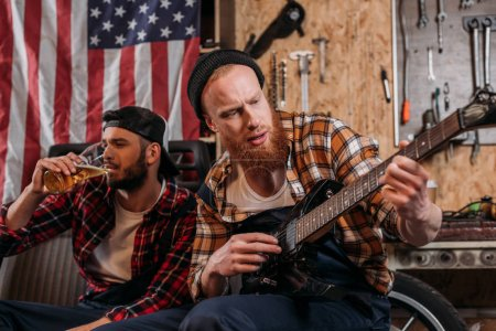 handsome mechanics playing guitar and drinking beer at garage