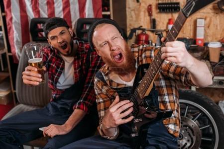drunk mechanics playing guitar and drinking beer at garage
