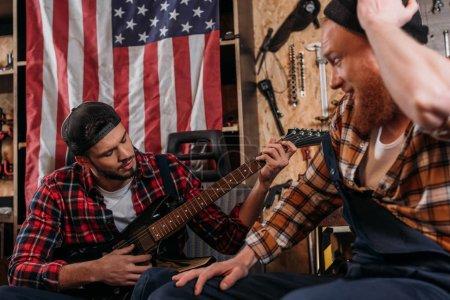 handsome mechanics playing guitar at garage