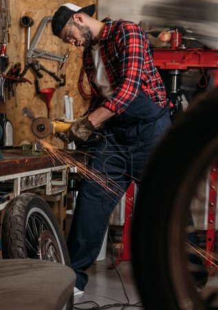 handsome bike repair station worker using electric circular saw at garage