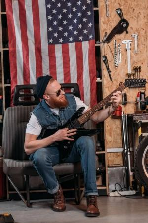 handsome bearded man playing electric guitar at garage with usa flag hanging on wall