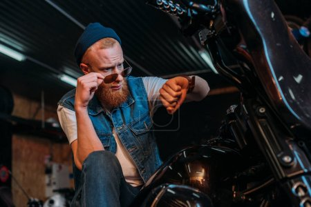 handsome young man in sunglasses looking at watch while sitting on motorcycle at garage