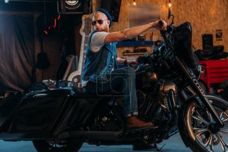 handsome young man sitting on motorcycle at garage