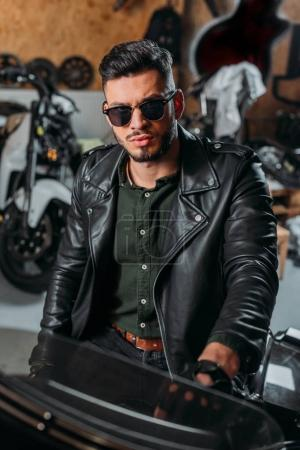 handsome rockabilly man sitting on bike at garage