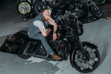 high angle view of handsome young man on bike at garage and looking at camera