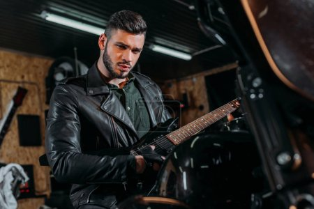handsome young man playing guitar while sitting on bike at garage