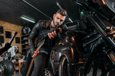 handsome young man sitting on bike with guitar at garage