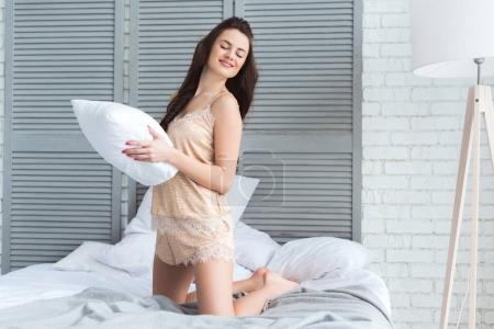 smiling attractive woman in pajamas with pillow in hands on bed