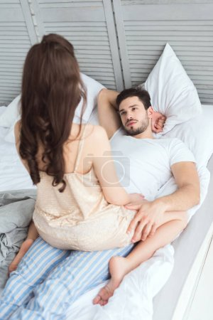 Photo for Partial view of young man looking at girlfriend in pajamas on bed - Royalty Free Image