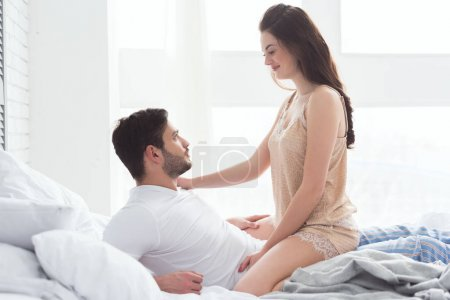 side view of young couple in pajamas looking at each other on bed at home
