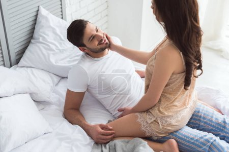Photo for Partial view of young smiling man looking at girlfriend on bed - Royalty Free Image