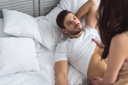 Photo for Partial view of young man looking at girlfriend on bed - Royalty Free Image