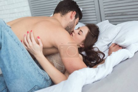 young sexy couple kissing on bed at home