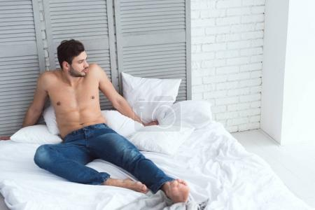 young attractive man in jeans lying on bed