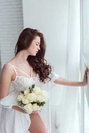 side view of young woman in underwear with bouquet of roses standing at window