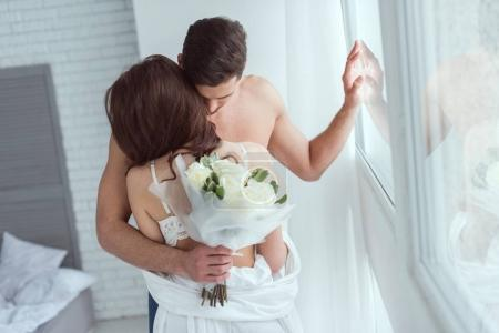 shirtless man with bouquet of roses hugging girlfriend at home