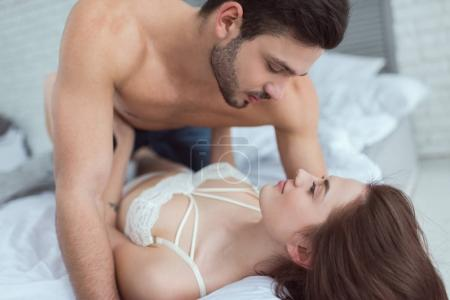 portrait of young seductive couple on bed at home