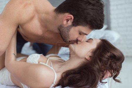 Photo pour Vue de côté du jeune homme embrasser séduisante copine en sous-vêtements sur le lit à la maison - image libre de droit
