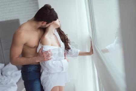 Photo for Side view of young sexy couple standing at window at home - Royalty Free Image