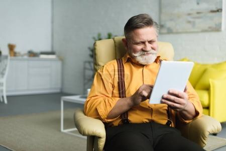 Photo pour Homme âgé barbu souriant utilisant une tablette numérique à la maison - image libre de droit