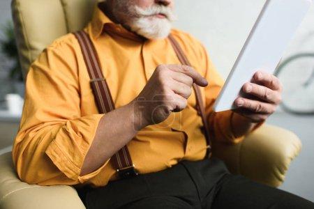 cropped shot of bearded senior man using digital tablet at home