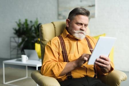 Photo pour Bel homme âgé barbu utilisant une tablette numérique à la maison - image libre de droit