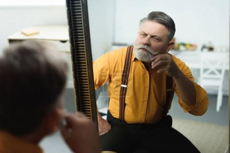 handsome bearded senior man trimming moustache with scissors and looking at mirror