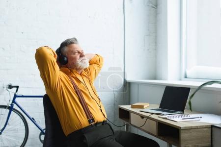 Photo pour Homme âgé détendu dans les écouteurs reposant avec les mains derrière la tête et regardant loin tout en utilisant un ordinateur portable avec écran blanc à la maison - image libre de droit