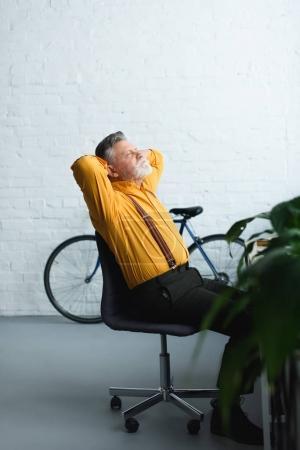 vue de côté de haut barbu assis avec les mains derrière la tête sur la chaise