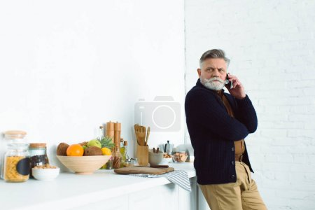 bearded senior man talking by smartphone while standing at kitchen and looking away