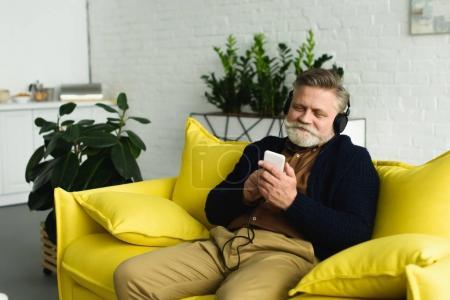 Photo pour Homme âgé barbu souriant dans les écouteurs assis sur le canapé et écouter de la musique avec smartphone - image libre de droit