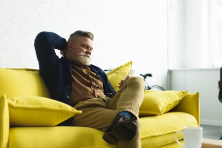 smiling bearded senior man using smartphone while sitting on sofa at home