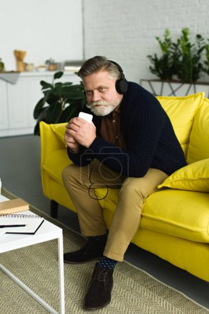 handsome smiling senior man in headphones listening music with smartphone