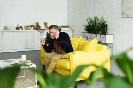 Photo for Selective focus of senior man talking by smartphone and looking away while sitting on sofa at home - Royalty Free Image