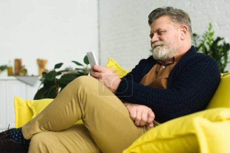Photo pour Homme âgé barbu souriant assis sur le canapé et utilisant un smartphone - image libre de droit