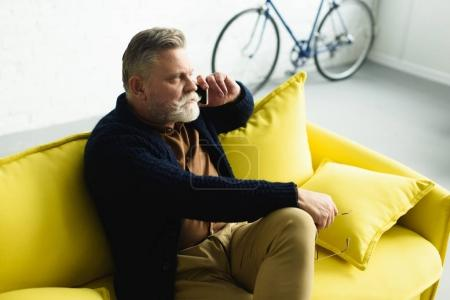 Photo for Bearded senior man talking by smartphone and looking away while sitting on sofa at home - Royalty Free Image