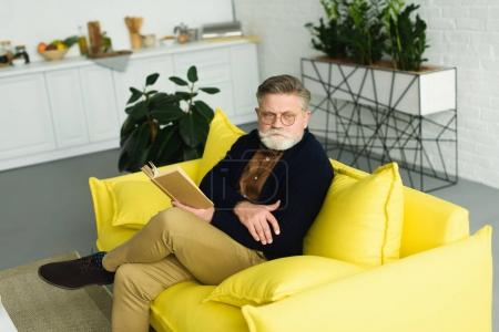 Photo pour Vue grand angle de l'homme âgé en lunettes assis sur le canapé et le livre de lecture - image libre de droit