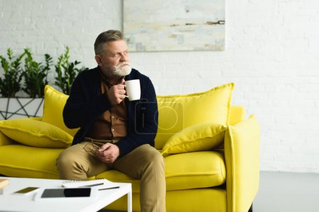 pensive senior man holding cup of tea while sitting on yellow couch and looking away at home