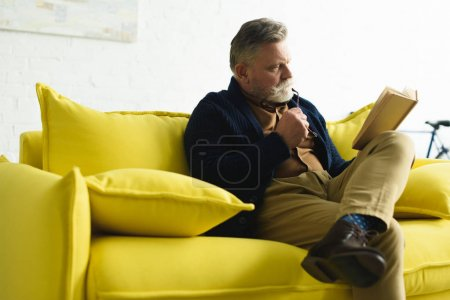 Photo for Bearded senior man sitting on yellow couch and reading book - Royalty Free Image