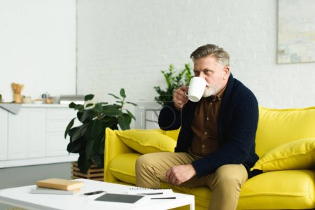 Photo pour Senior assis sur un canapé jaune et buvant du thé à la maison - image libre de droit
