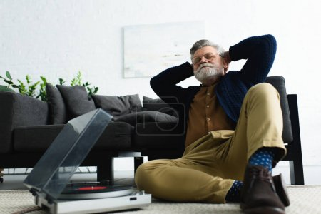 relaxed stylish man in eyeglasses sitting with hands behind head and listening music with vinyl record player at home