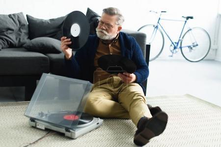 Photo pour Élégant homme âgé tenant des disques vinyle tout en étant assis sur le tapis à la maison - image libre de droit