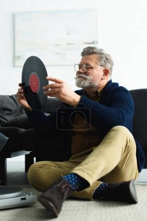 smiling stylish senior man in eyeglasses holding vinyl record while sitting on carpet