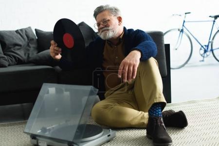 Photo pour Souriant bel homme âgé dans les lunettes tenant disque de vinyle tout en étant assis sur le tapis - image libre de droit