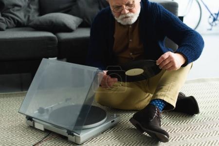 Photo pour Plan recadré d'un homme âgé portant des lunettes tenant un record de vinyle assis sur un tapis - image libre de droit