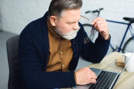 concentrated senior man holding eyeglasses and using laptop