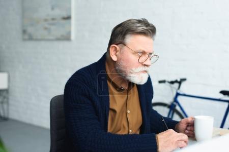 Foto de Hombre senior pensativo en anteojos sosteniendo la taza y el tomar notas en casa - Imagen libre de derechos