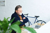 selective focus of confident man in eyeglasses sitting with crossed arms and using laptop